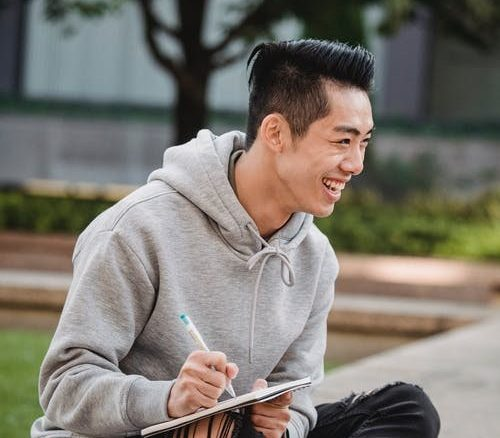 AAPI man smiling and writing in notepad